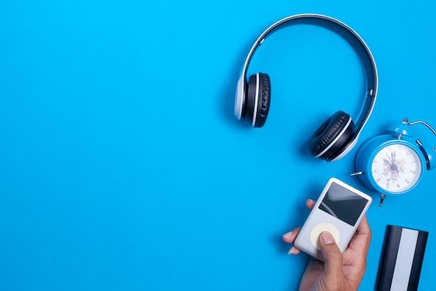 Fone de ouvido sem fio e media player, despertador azul sobre fundo de papel azul