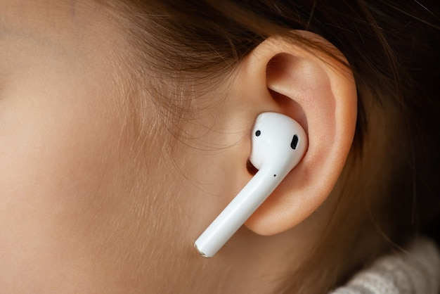 Fone de ouvido sem fio no ouvido feminino