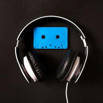 Fone de ouvido sobre a fita cassete azul sobre fundo preto