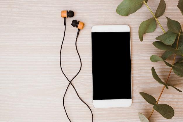 Fone de ouvido; telefone celular e folhas no fundo de madeira