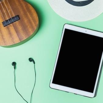 Fone de ouvido; violão; chapéu e tablet digital em fundo turquesa