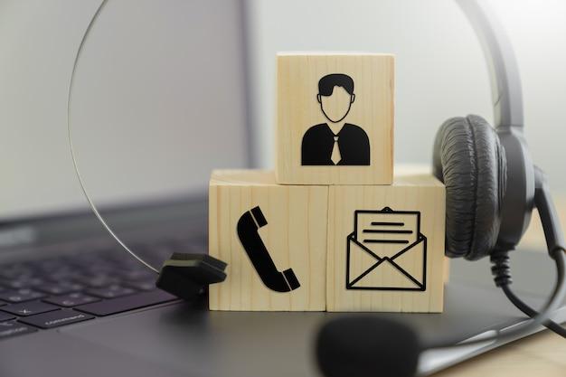 Fone de ouvido voip e comunicação de ícone no bloco de madeira. conceito de suporte de call center.