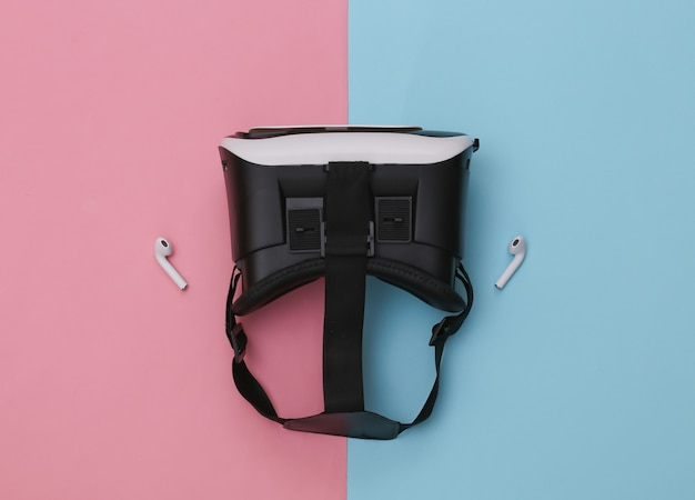 Fone de ouvido vr e fones de ouvido sem fio em fundo azul-rosa pastel.