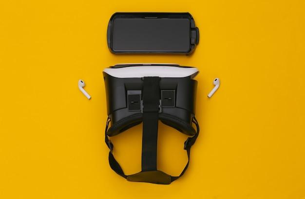 Fone de ouvido vr, smartphone e fones de ouvido sem fio em fundo amarelo.