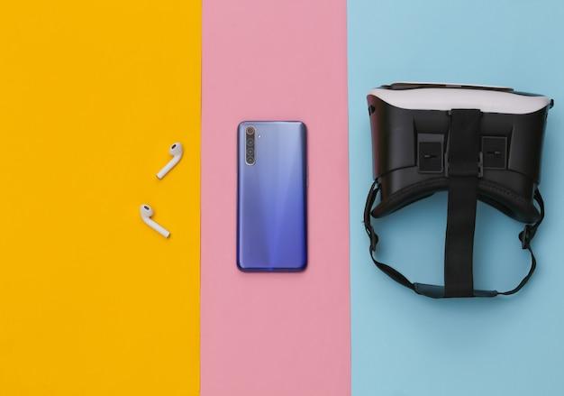 Fone de ouvido vr, smartphone e fones de ouvido sem fio em fundo colorido pastel.