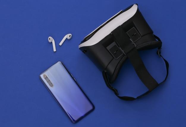 Fone de ouvido vr, smartphone e fones de ouvido sem fio no fundo azul clássico.
