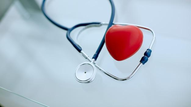 Fonendoscópio e coração vermelho na mesa