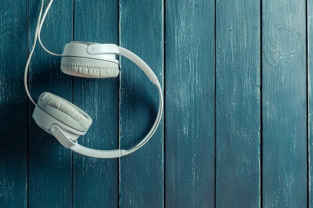 Fones de ouvido áudio portátil moderno na placa de madeira