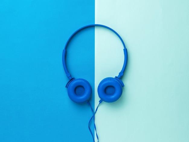 Fones de ouvido azuis brilhantes sobre um fundo de dois tons. equipamento móvel de reprodução de áudio.