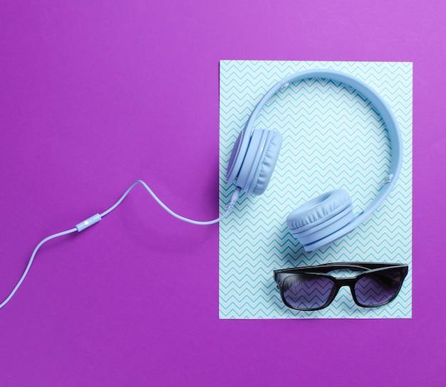 Fones de ouvido azuis com cabo, óculos de sol no fundo criativo roxo azul