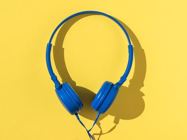 Fones de ouvido azuis em uma luz brilhante sobre um fundo amarelo. equipamento móvel de reprodução de áudio.