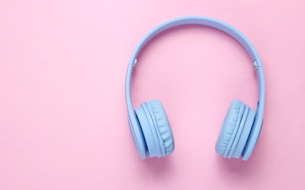 Fones de ouvido azuis sem fio modernos em um fundo rosa pastel