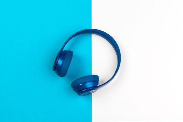 Fones de ouvido azuis sobre fundo de cor azul e branco