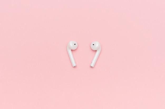 Fones de ouvido bluetooth sem fio branco sobre fundo rosa pastel