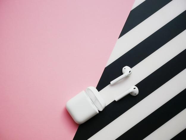 Fones de ouvido brancos com caixa em preto e rosa