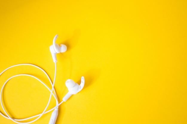 Fones de ouvido brancos com fio em uma parede amarela