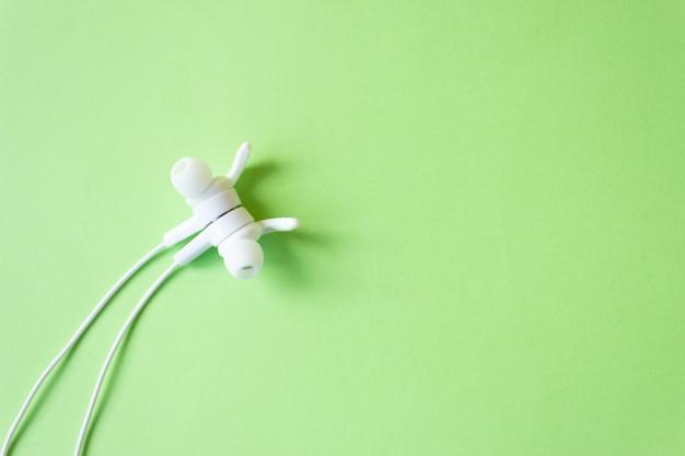 Fones de ouvido brancos com fio em uma parede verde