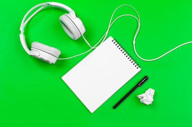 Fones de ouvido brancos com fio sobre fundo verde brilhante