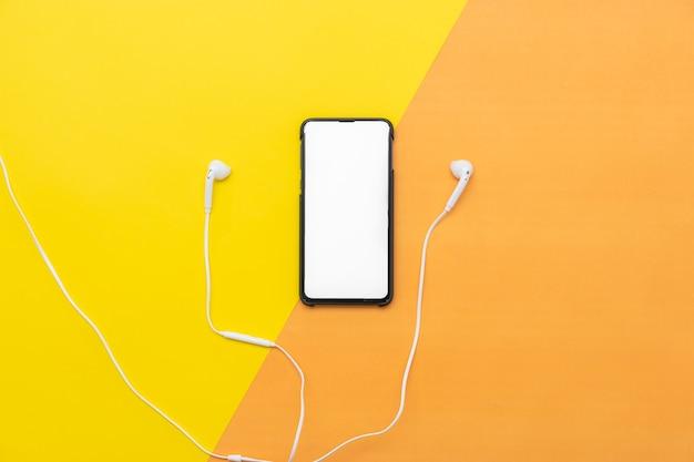 Fones de ouvido brancos com o telefone isolado em fundo amarelo / laranja.