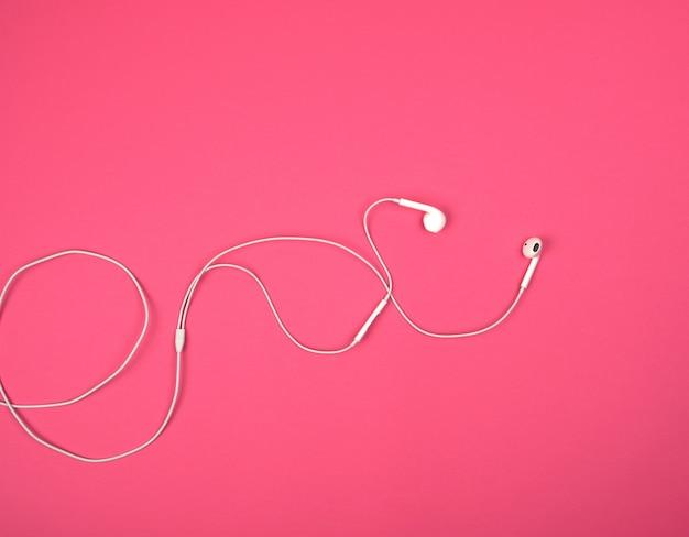 Fones de ouvido brancos com um cabo em um fundo rosa