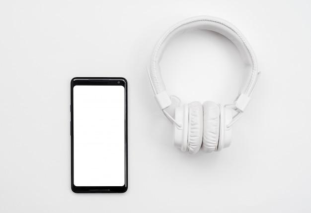 Fones de ouvido brancos e telefone inteligente em fundo branco