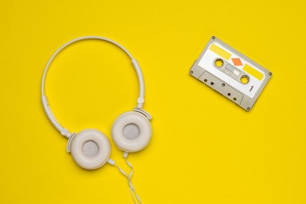Fones de ouvido brancos e um gravador em um fundo amarelo.