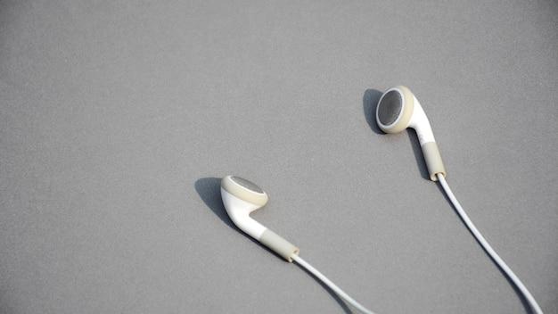 Fones de ouvido brancos em fundo cinza