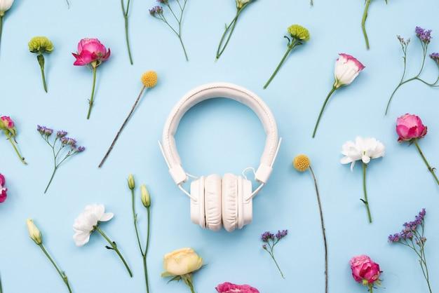 Fones de ouvido brancos em um conceito floral, música