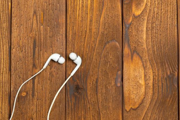 Fones de ouvido brancos na mesa de madeira