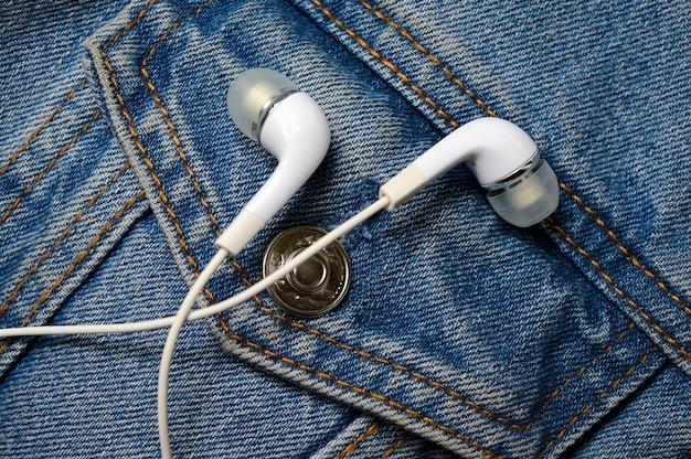 Fones de ouvido brancos para o telefone no fundo de uma jaqueta jeans. fechar-se.