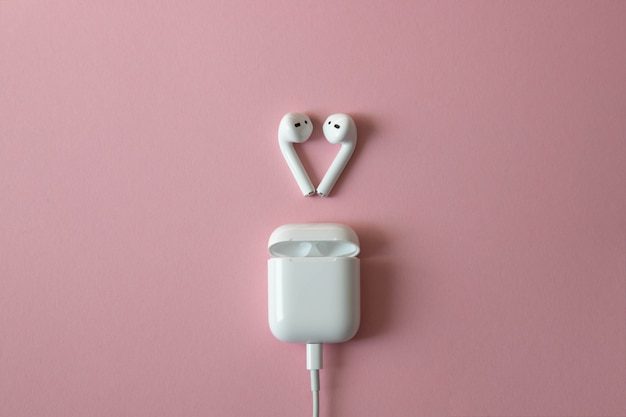 Fones de ouvido brancos sem fio com carregador ligado em fundo rosa