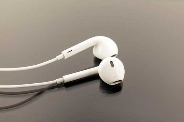 Fones de ouvido brancos sobre fundo preto