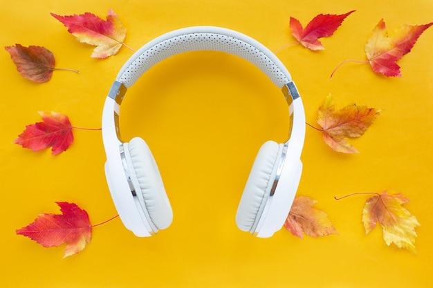 Fones de ouvido brancos sobre um fundo amarelo com folhas vermelho-amarelas. postura plana