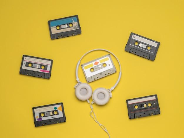 Fones de ouvido brancos sobre um fundo de cassetes de fita espalhadas em um fundo amarelo. ferramentas vintage de armazenamento e reprodução de gravação de áudio.