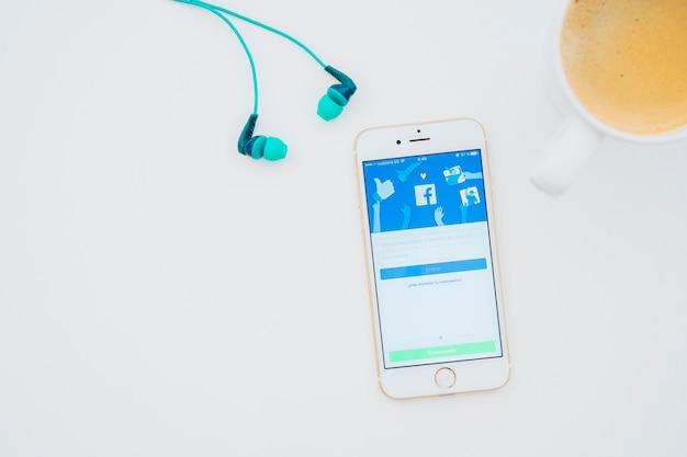 Fones de ouvido, caneca de café e telefone com aplicativo do facebook