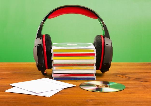 Fones de ouvido com cds em uma mesa de madeira, em uma parede verde.