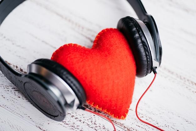 Fones de ouvido com coração vermelho na mesa