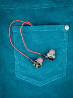 Fones de ouvido com design original saindo do bolso da calça jeans verde. o conceito de moda moderna para dispositivos eletrônicos.