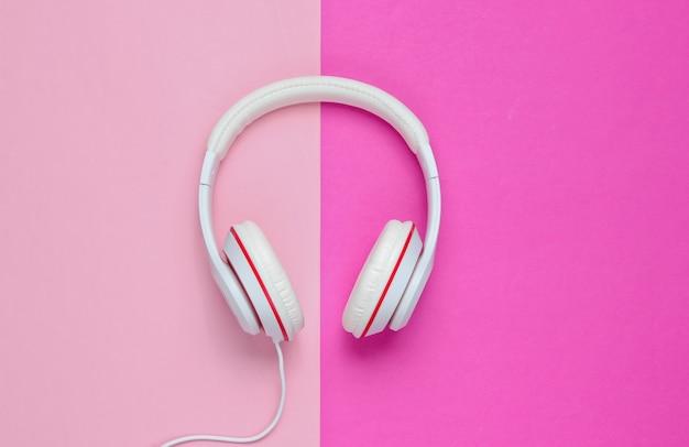 Fones de ouvido com fio brancos clássicos em fundo de papel colorido. estilo retrô. anos 80. cultura pop. conceito de música mínima