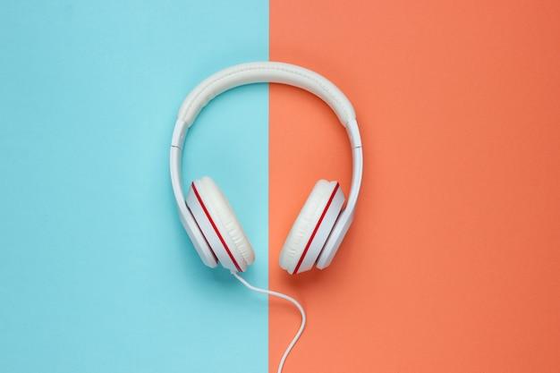 Fones de ouvido com fio brancos clássicos em fundo de papel colorido. estilo retrô. anos 80. cultura pop. vista do topo. conceito de música mínima
