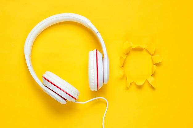 Fones de ouvido com fio brancos clássicos sobre fundo de papel amarelo roxo com orifício rasgado. estilo retrô. anos 80. cultura pop.