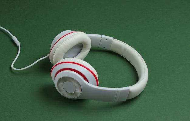 Fones de ouvido com fio brancos clássicos sobre fundo de papel verde. estilo retrô. anos 80. cultura pop. amante da música