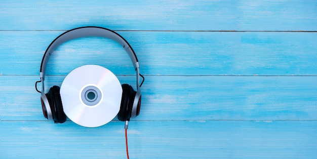 Fones de ouvido com fio com disco compacto sobre fundo azul pastel. estilo retrô, dj. vista superior do conceito de música