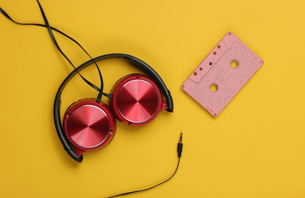 Fones de ouvido com fio com fita cassete em fundo amarelo