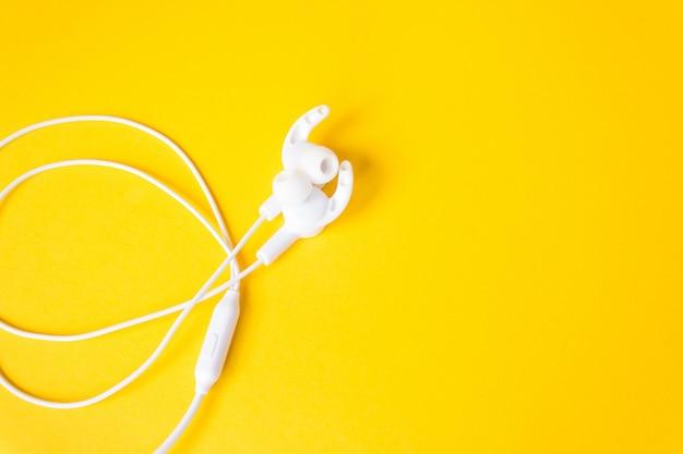 Fones de ouvido com fio em uma parede amarela brilhante. copie o espaço