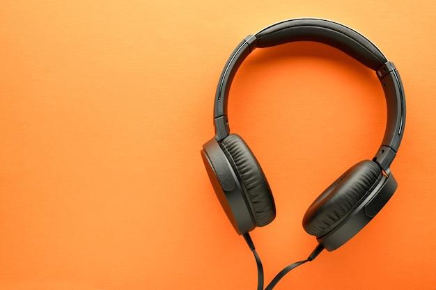 Fones de ouvido com fio preto em fundo laranja. conceito de entretenimento