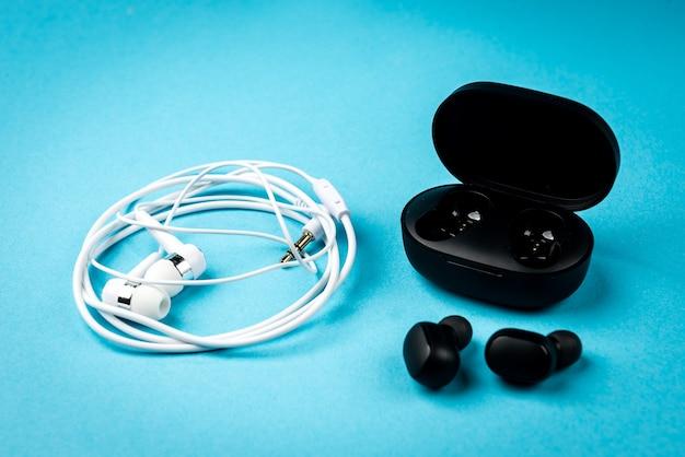 Fones de ouvido com fio pretos e brancos sobre fundo azul.