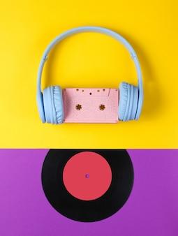 Fones de ouvido com fita cassete, registro lp em fundo roxo-amarelo