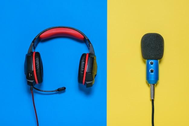 Fones de ouvido com microfone em fundo amarelo e azul. a vista do topo.