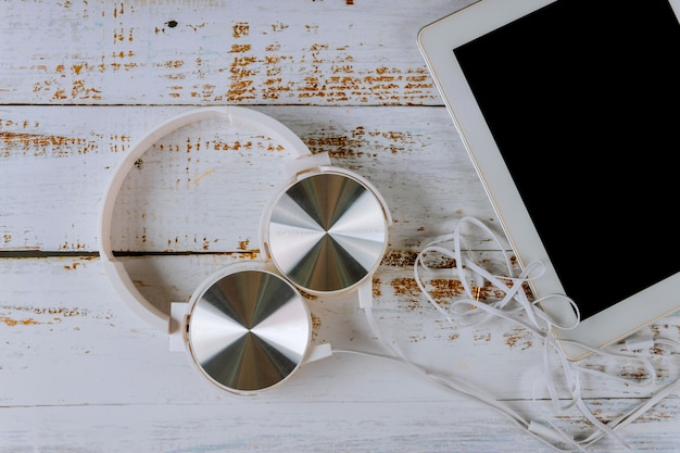 Fones de ouvido com tablet em fundo branco de madeira